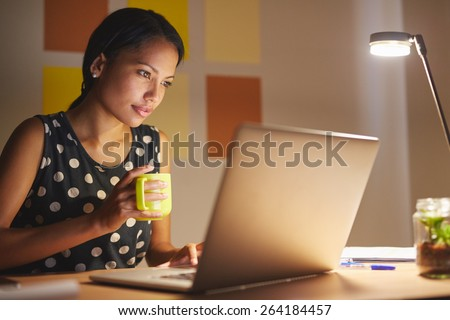 A young woman working on her laptop in her office at night - stock photo