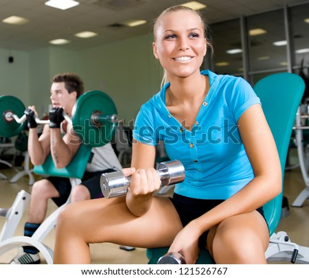 A young women lifting free weights with a confident smile - stock photo