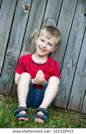 A young 4 year old boy is sitting outside against a rustic fence.  He has a red shirt and a big smile.   - stock photo
