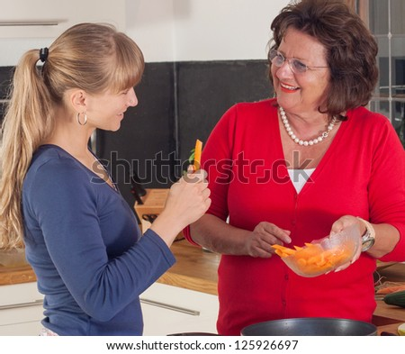 A younger and a older women are cooking in a kitchen and have fun together - stock photo