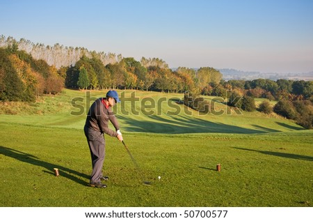 A younger male golfer teeing off on a bright autumn morning. Motion blur on the clubhead, with blue sky in the background, and copyspace for your text/design. - stock photo