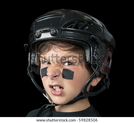 A youth hockey player wearing protective headware snarls at the camera - stock photo