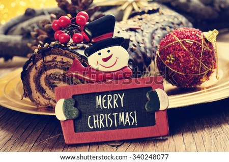 a yule log cake, traditional of christmas time, and a snowman-shaped chalkboard with text merry christmas written in it - stock photo