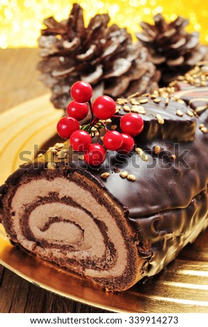 a yule log cake, traditional of christmas time, in a golden tray with some natural ornaments, such as pinecones - stock photo