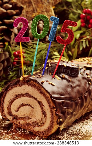 a yule log cake, traditional of christmas time, with glittering numbers of different colors forming the number 2015, as the new year - stock photo