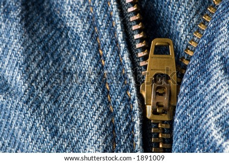 A zipper on a pair of denim blue jeans partially open - stock photo