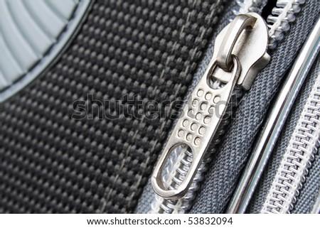 A zipper on the grayish suitcase closeup photo - stock photo