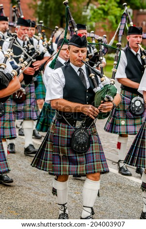 AABENRAA, DENMARK - JULY 6 - 2014: Scottish bagpipe band is marching down the street at the  - stock photo