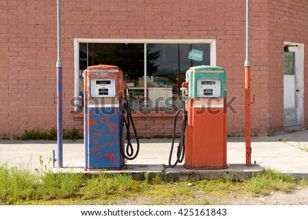 Abandoned and closed vintage fuel pump with garage  at petrol station. / Abandoned Fuel Pump - stock photo