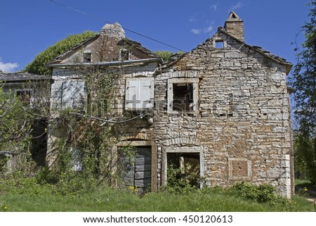 Abandoned and dilapidated houses idyllic overgrown with plants characterize the idyllic landscape - stock photo