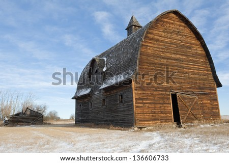 abandoned barn and collapsed log house - stock photo