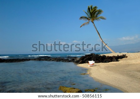Abandoned beach chair sits on the sands of the Kohala Coast on the Big Island of Hawaii.  Leaning palm tree stands guard over this quiet stretch of beach. - stock photo