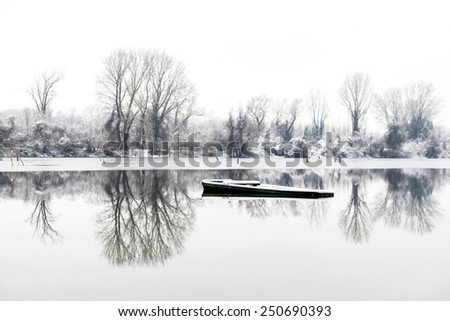 abandoned boat in a frozen lake winter in Novi Sad Serbia - stock photo