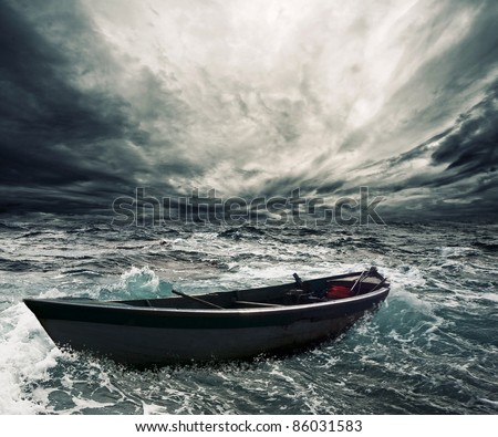Abandoned boat in stormy sea - stock photo