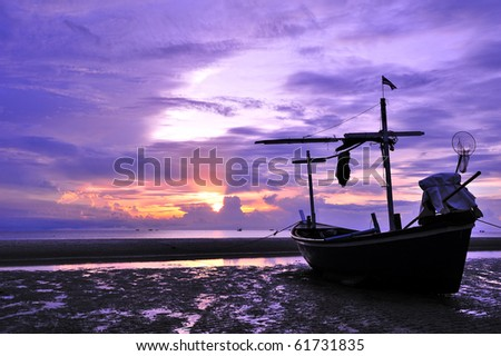 Abandoned boat in twilight in purple and red - stock photo