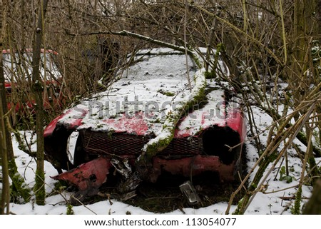 abandoned car in the snow in an overgrown woods - stock photo