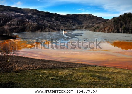 Abandoned church in the middle of a lake full with mining residuals - stock photo