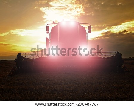 Abandoned combine harvest wheat with lighted main lights in the middle of a farm field. Morning yellow wheat field. The sunset cloudy orange sky. - stock photo