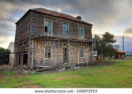 Abandoned dilapidated two storey late Victorian Georgian farm house with corrugated iron roof  and brick fireplace.  It once had an upper storey verandah with fancy wrought iron lattice work.  - stock photo