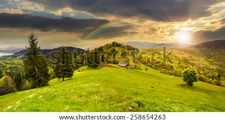 abandoned farm field with ruined barn in mountains near coniferous forest in sunset light with rainbow - stock photo