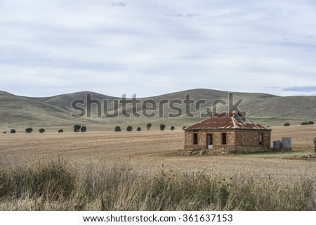 Abandoned farm house on a rural farm built from stone and iron - stock photo