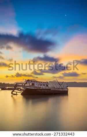 Abandoned fishing boat at sunset, Thailand. - stock photo
