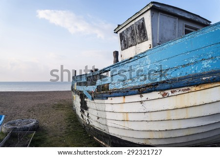 Abandoned fishing boat on beach during lovely Summer morning - stock photo