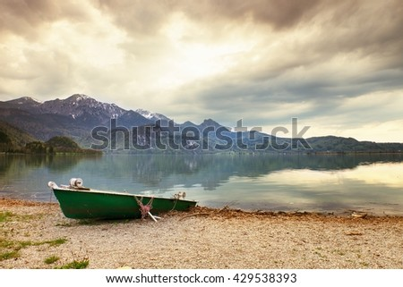 Abandoned fishing paddle boat on bank of Alps lake. Morning lake glowing by sunlight. Dramatic and picturesque scene. Mountains in water mirror. - stock photo