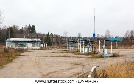 abandoned gas station and rusty pump at autumn day in Russia - stock photo