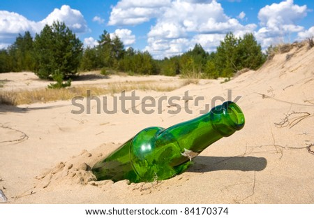 Abandoned green glass bottle in sands - stock photo