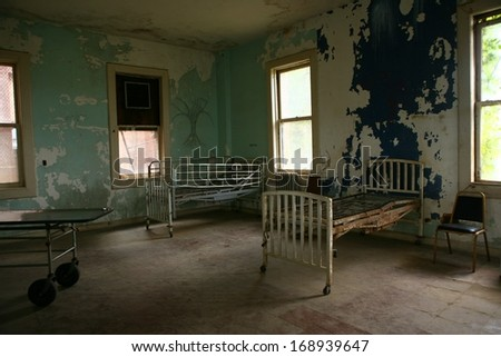 Abandoned Hospital Building With Empty Rusted Beds - stock photo