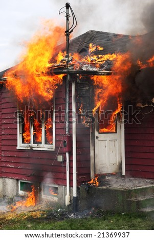 Abandoned house burning, with flames through windows and door - stock photo