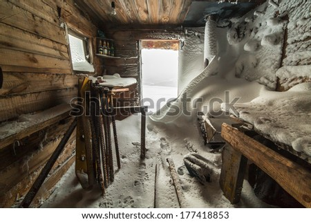 abandoned house covered with snow - stock photo