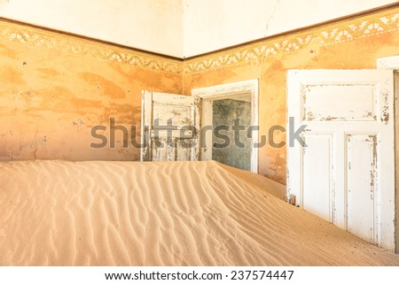 Abandoned house full of sand from the desert in the forsaken ghost town of Kolmanskop - Sightseeing around Luderitz in Namibia - African wonders and mysteries - stock photo