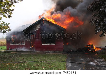 Abandoned house in flame, house is still up but flames are all over - stock photo