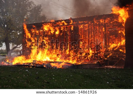Abandoned house in flame , partly collapsed - stock photo