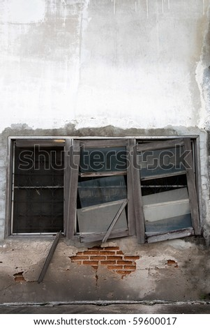 abandoned house with broken window and brick wall - stock photo