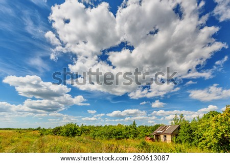 Abandoned hut among trees and bushes beneath cloudy sky in summertime - stock photo