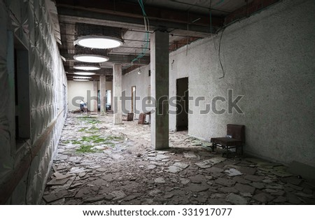 Abandoned industrial building interior. Green moss grow under round illumination holes in ceiling  - stock photo