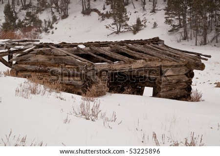 Abandoned log cabin won't provide much shelter from the snowstorm with much of it's roof gone - stock photo