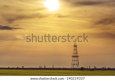 Abandoned oil rig profiled on evening sky - stock photo