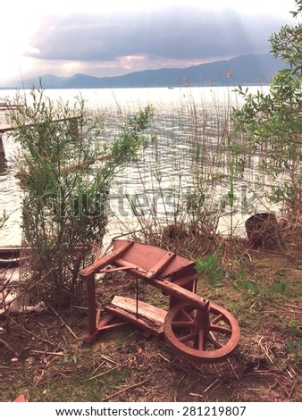 Abandoned old broken wheelbarrow laying on the side on the shore of a lake  - stock photo