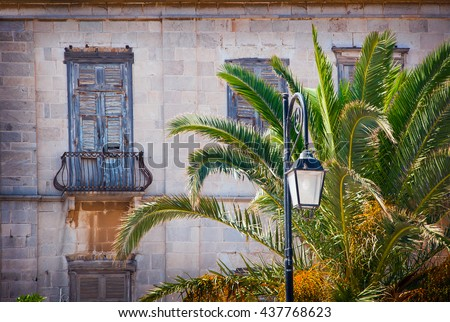 Abandoned old building with wooden shutters and balconies. - stock photo