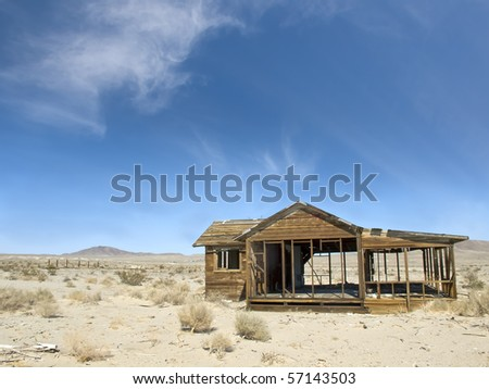 Abandoned old house surrounded by beautiful blue sky and desert sands. Decaying wooden structures show weathering from desertion. - stock photo
