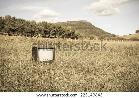 Abandoned old or antique tv in the grass field - stock photo
