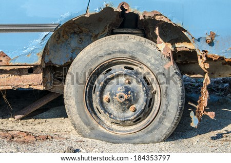 Abandoned old rusty car on the meadow - close-up - stock photo