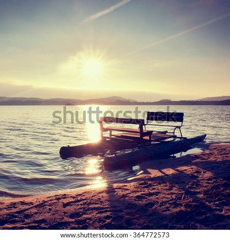 Abandoned old rusty pedal boat stuck on sand of beach. Wavy water level, island on horizon. Autumn weather at coastline  - stock photo