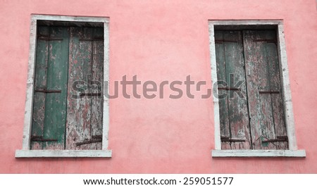 Abandoned palazzo in Venice (Italy). Pink stucco wall and closed wooden shutters with peeling paint.  - stock photo