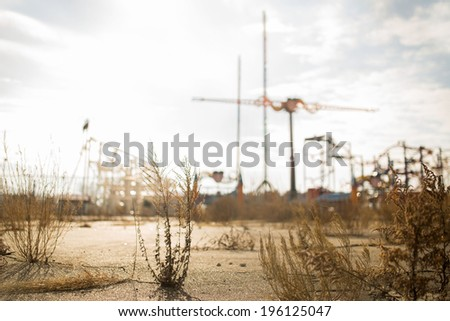 Abandoned Parking Lot With Cranes and Amusement Rides in the Background - stock photo