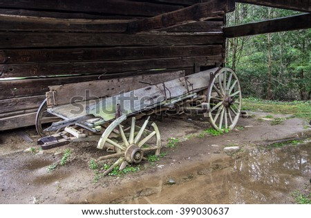Abandoned Pioneer Wagon. Abandoned pioneer wagon left to deteriorate beside a barn. Great Smoky Mountain National Park. Gatlinburg, Tennessee. - stock photo